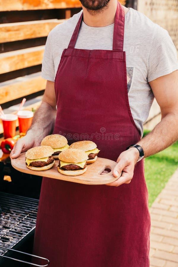 的人拿着委员会用汉堡的特写镜头观点在格栅烹调了户外 免版税库存照片