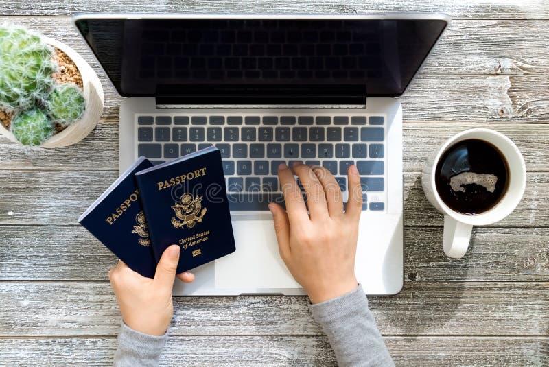 的人持美国护照,当使用膝上型计算机时 库存照片