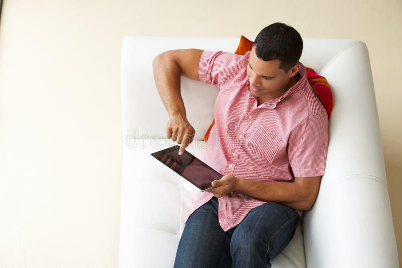 的人放松在沙发观看的电视上的顶上的观点 免版税图库摄影