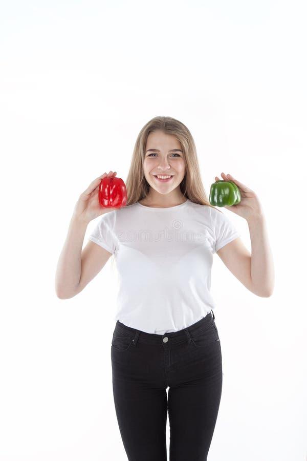的关闭拿着红色和绿色甜椒年轻人和微笑的妇女 健康饮食和维生素 素食食物 免版税库存照片