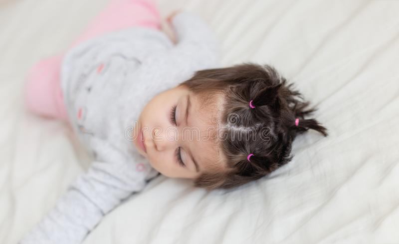 的可爱宝贝女孩睡觉在床上的画象观点 库存照片