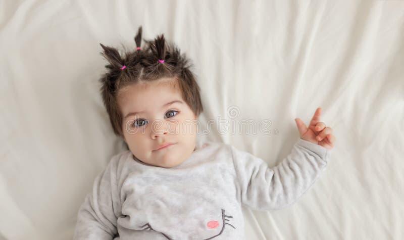 的可爱宝贝女孩说谎在床上的画象观点 图库摄影