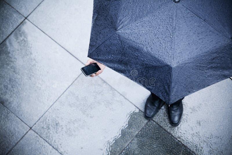的商人拿着伞和在雨中的大角度观点看他的电话 免版税库存图片