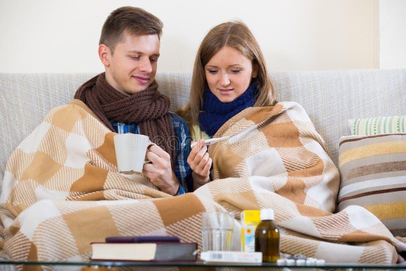冻结的夫妇坐长沙发在有温度计的毯子下 库存图片