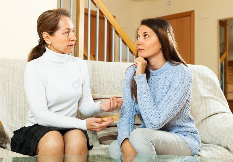 的女儿和有成熟的母亲严肃谈话 免版税库存照片