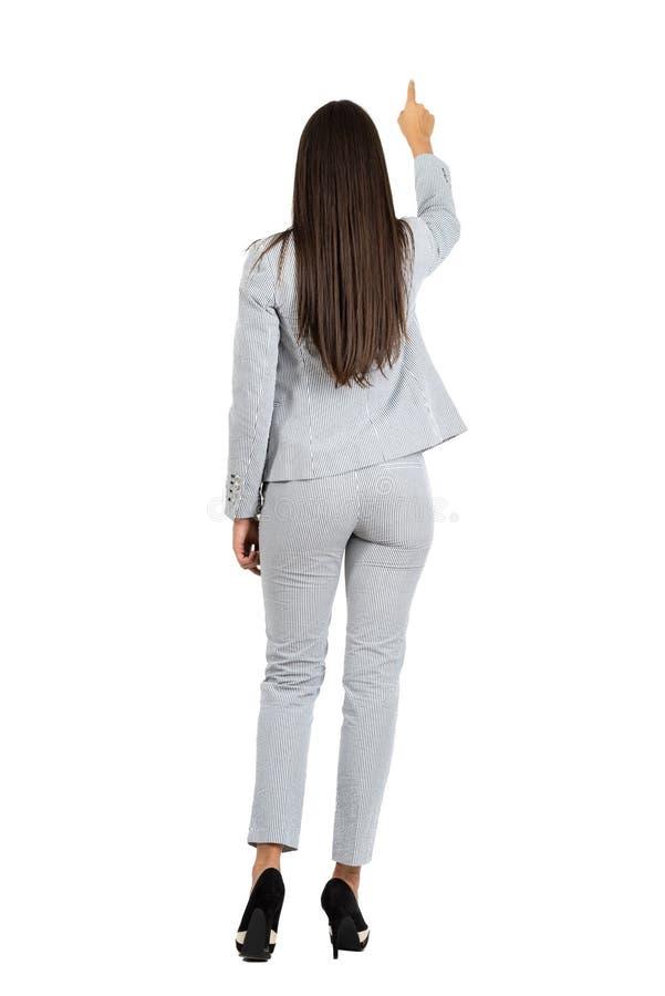 的女商人指向在她前面的后面观点手指 免版税图库摄影