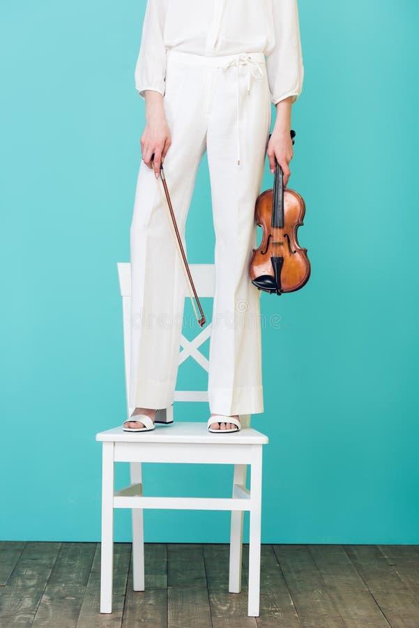 的女孩举行小提琴和身分在椅子的播种的观点, 免版税图库摄影