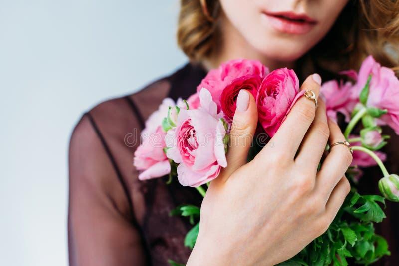 的女孩拿着嫩桃红色花的特写镜头观点 免版税库存图片