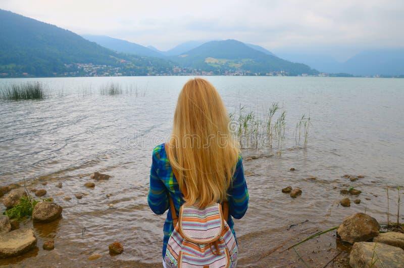 的女孩站立近的水和看与山的后面观点天际 库存照片