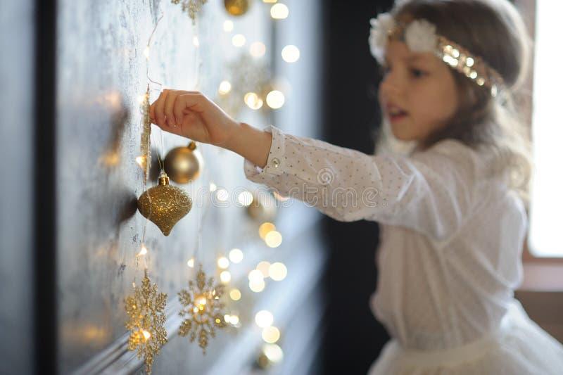 8-9年的女孩以欢欣敬佩金圣诞节树装饰 免版税库存图片