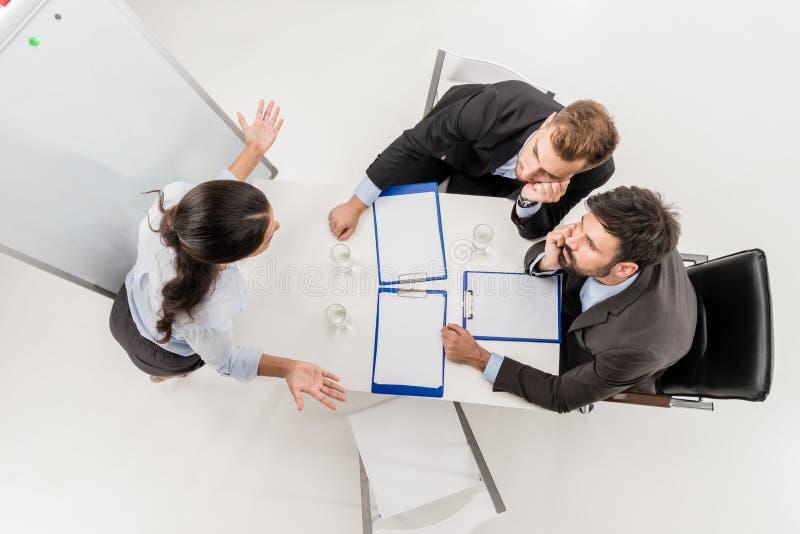 的女实业家解释战略的顶上的观点对乏味同事在会议期间 库存图片