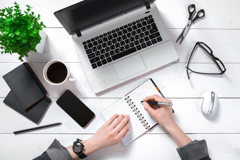 的女实业家运作在计算机的顶上的观点在办公室 库存图片