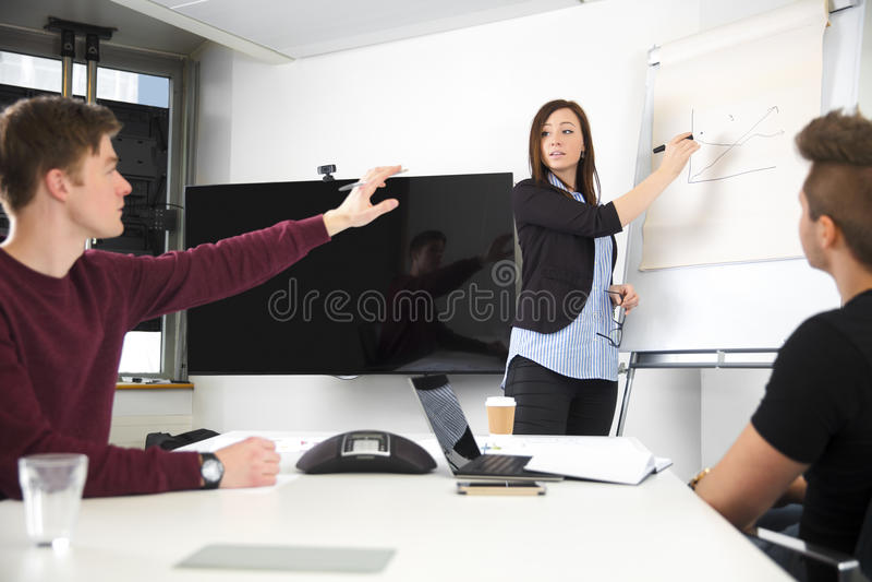 给介绍的女实业家,当看同事Rai时 免版税库存照片