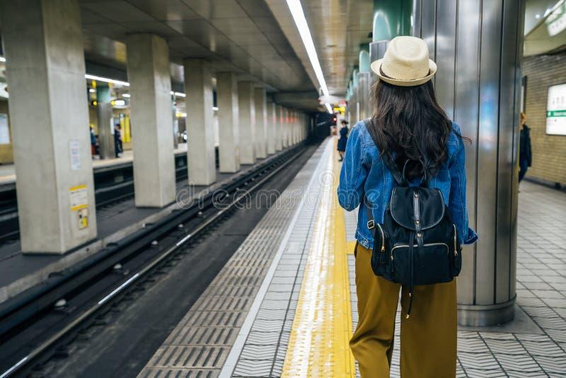 的女性背包徒步旅行者走在平台的后面观点在地铁在大阪日本 有长的黑色头发的年轻亚裔女孩 库存照片