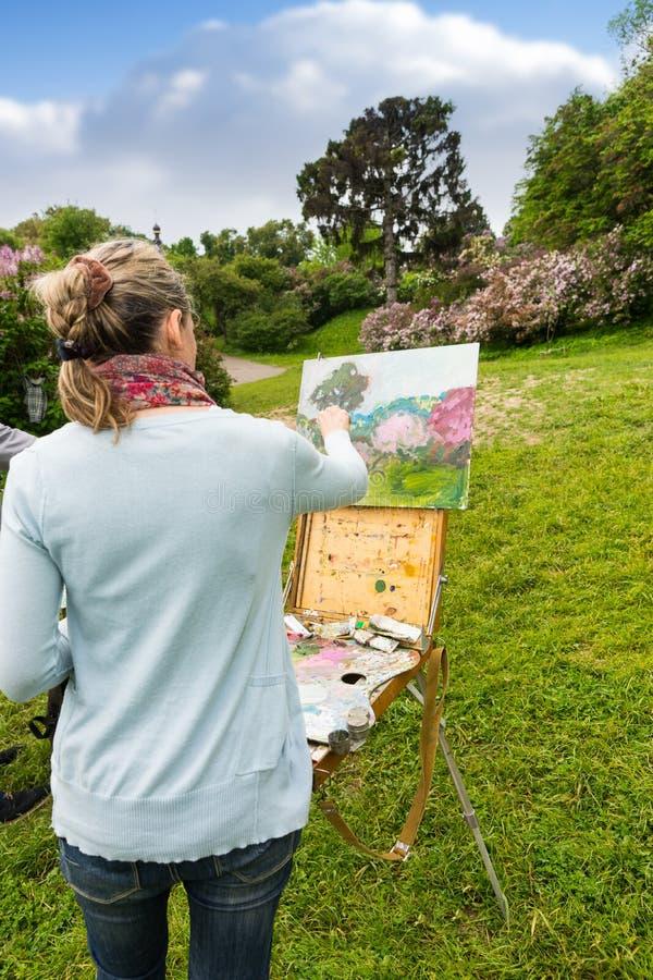 的女性艺术家完成她的图片的后面观点 免版税库存图片