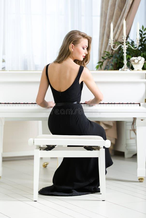 的女性音乐家坐和弹钢琴的后面观点 免版税库存照片