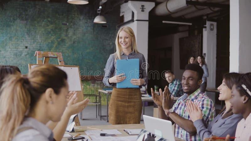 的女性经理走通过有文件的办公室的特写镜头观点 对女实业家的多种族队拍手 免版税图库摄影