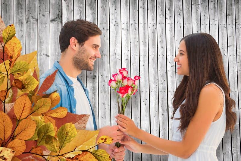 给他的女朋友玫瑰的愉快的行家的综合图象 免版税图库摄影