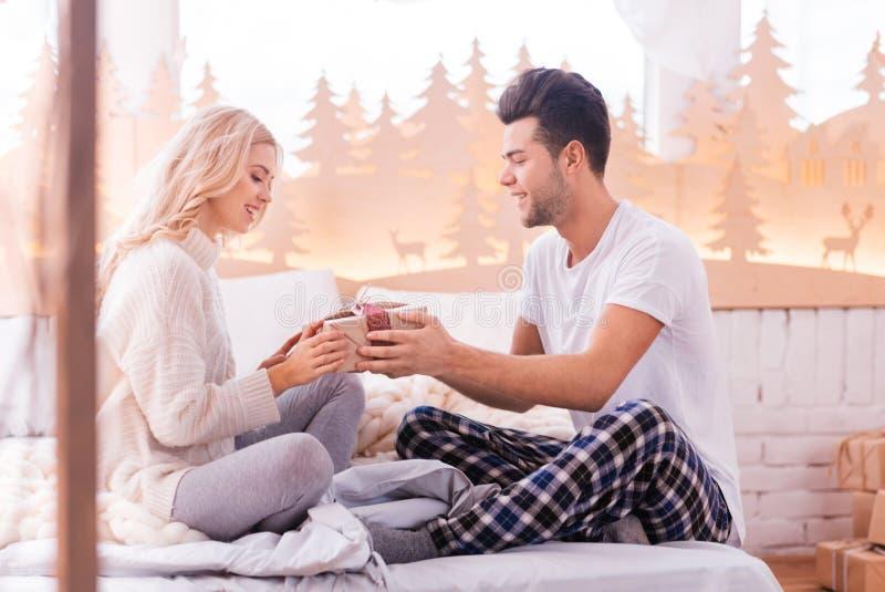给他的女朋友礼物的英俊的深色的人 免版税库存照片