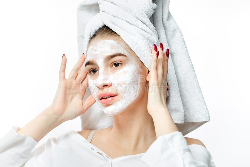 的好女孩有一块白色毛巾的白色衣裳在她的头发在她的面孔上把一个化妆面具放 免版税库存图片