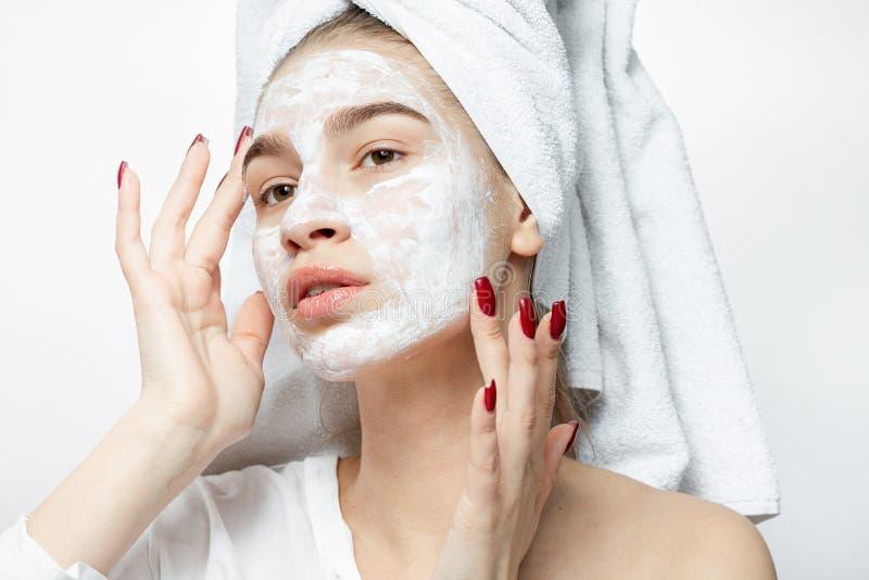 的好女孩有一块白色毛巾的白色衣裳在她的头发在她的面孔上把一个化妆面具放 免版税库存照片