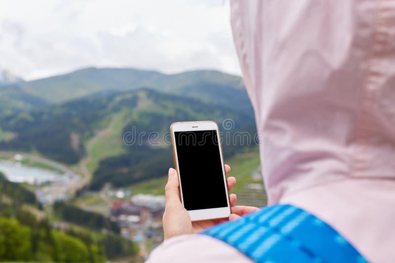 的妇女佩带玫瑰色夹克和蓝色背包的后面观点,站立在山顶部,拿着她的设备,没有图象,寻找 免版税库存照片
