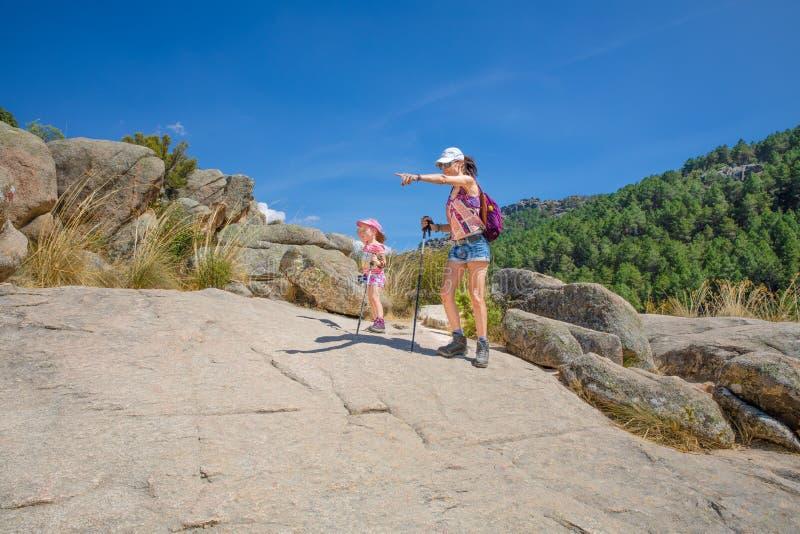 的妇女和冒险的小孩指向路线在Camorza峡谷在马德里附近 免版税库存图片
