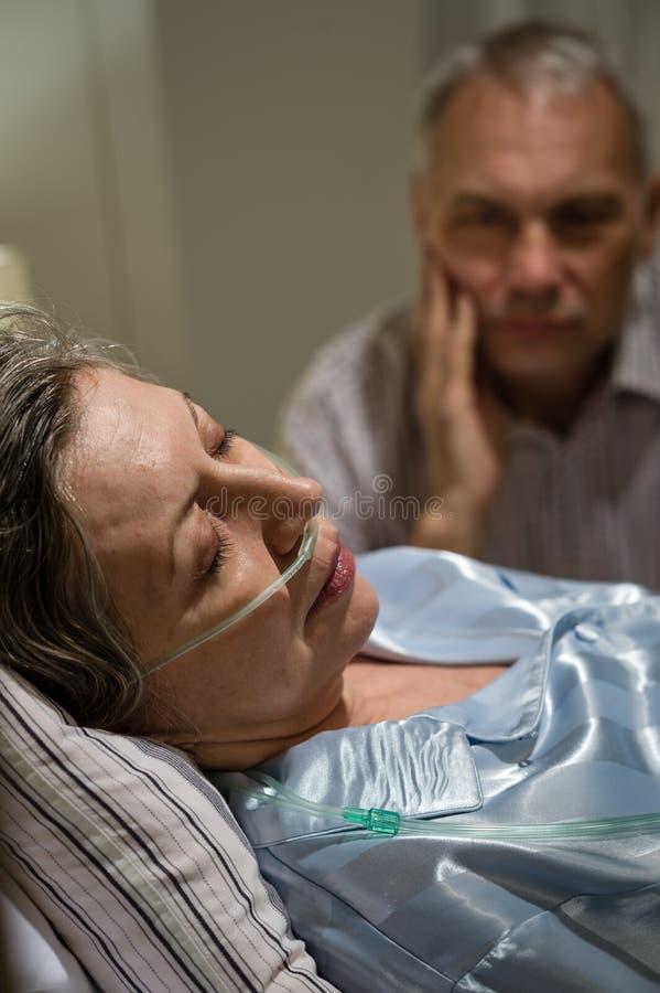 死的妇女在与有同情心的人的床上 库存图片