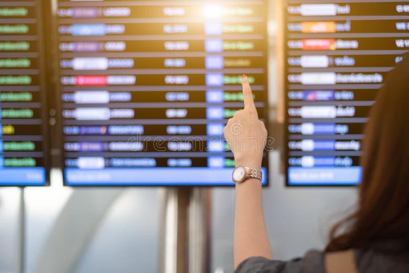 的妇女寻找从航行时刻表的后面观点飞行在机场 指向时间表的女性游人为离开飞机 库存图片