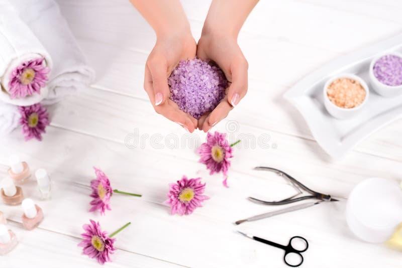 的妇女拿着在桌的部份观点海盐与花、毛巾、指甲油、奶油色容器和工具为修指甲 免版税库存照片