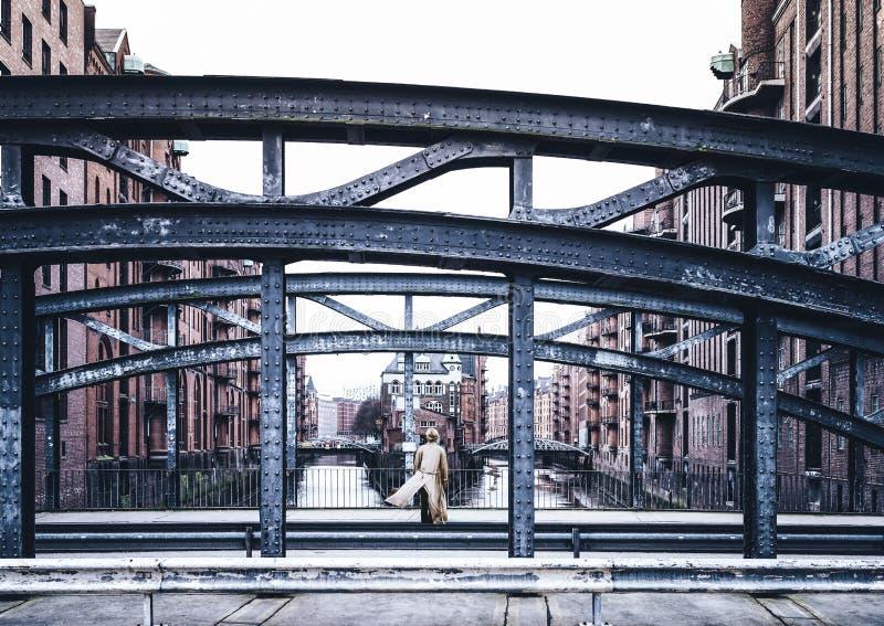 的妇女穿长的外套的后面观点站立在桥梁在老仓库区Speicherstadt在汉堡 免版税库存照片