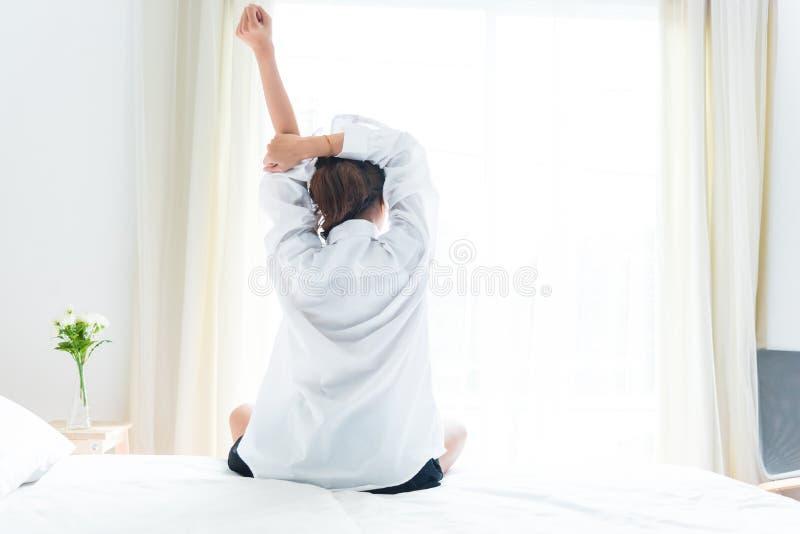 的妇女舒展在醒的早晨的后面观点在床上以后 免版税图库摄影
