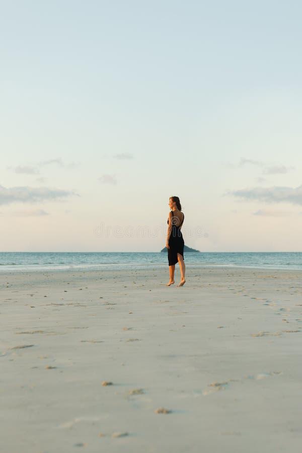 的妇女走在礼服的沙滩的观点 库存图片