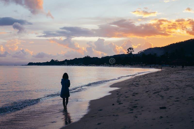 的孤独的妇女走在日落的海滩的后面观点 免版税库存照片