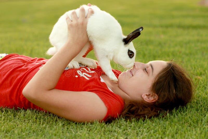 的孩子和使用她的宠物的兔宝宝户外 库存照片