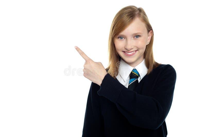 的安静和指向放松的青少年的女孩斜向一边 免版税库存图片