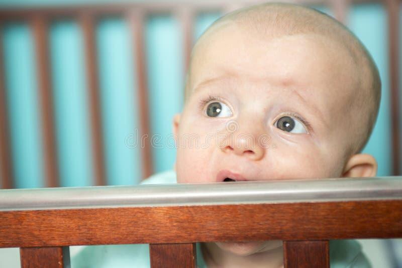 他的小儿床的可爱的婴孩 库存照片