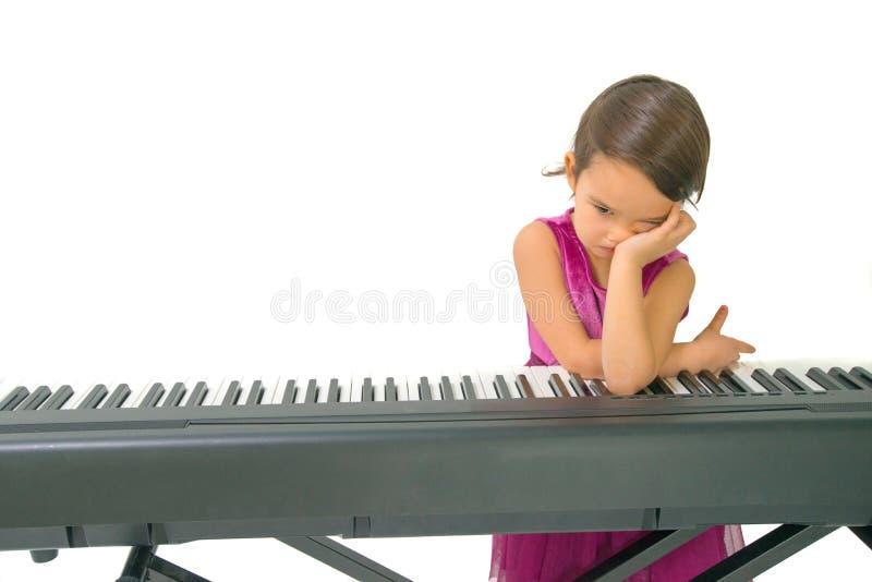 的小女孩疲乏,当实践钢琴时 免版税库存照片
