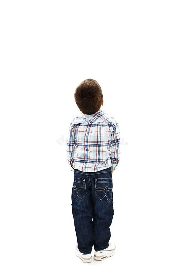 的小男孩看墙壁的后面观点 查出的背面图白色 免版税库存照片