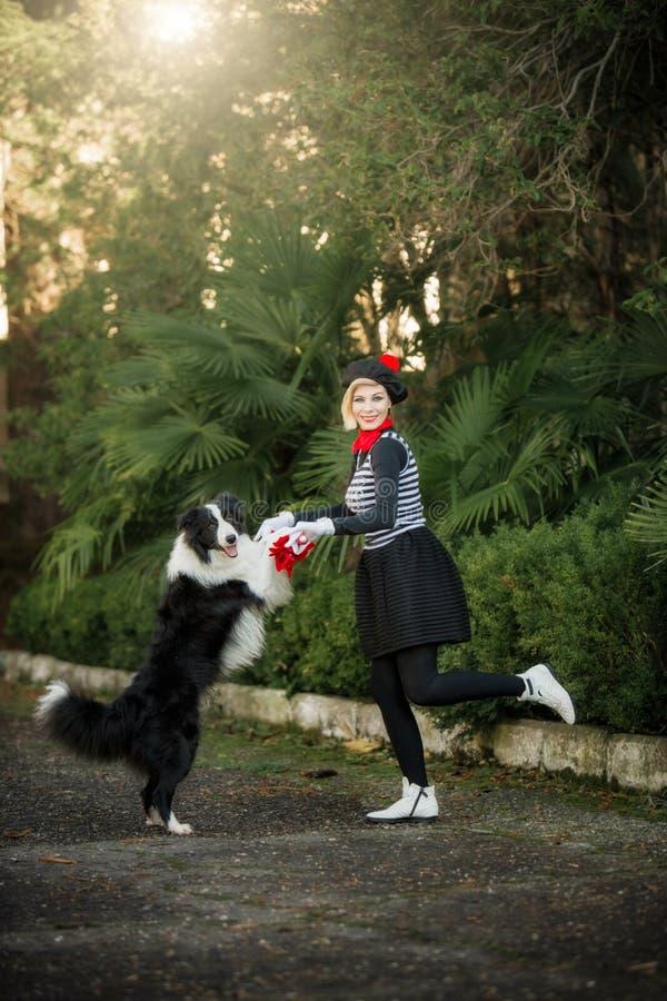 的少女和使用她的狗的博德牧羊犬户外 免版税库存图片