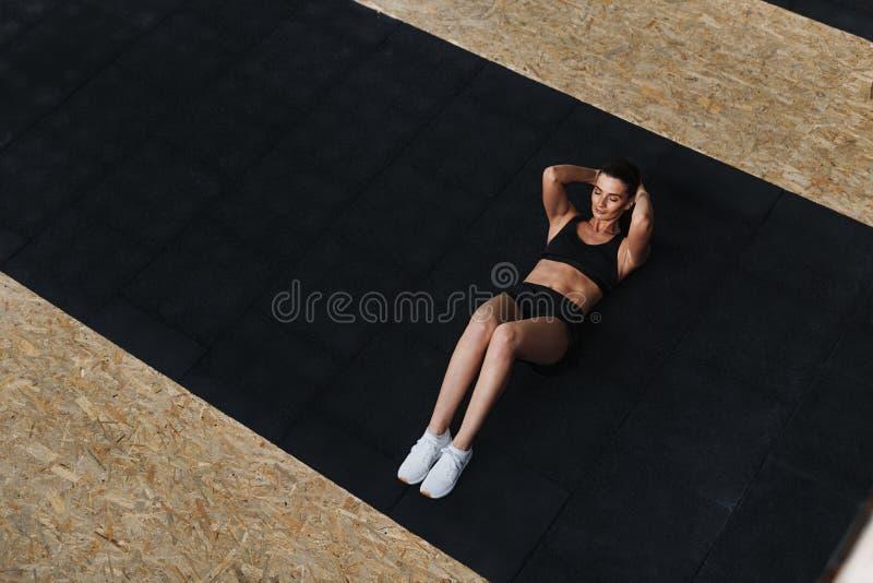 的少妇做仰卧起坐的大角度观点 图库摄影