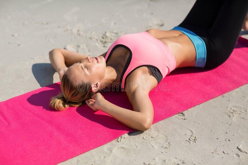 的少妇行使在锻炼席子的大角度观点 免版税库存图片