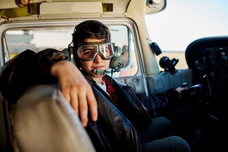 的少年男孩坐在小飞机,等待的爸爸驾驶舱内的观点来 库存照片