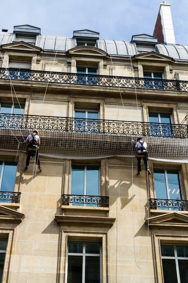 绳索的工作员在老居民住房前面,巴黎 免版税库存照片
