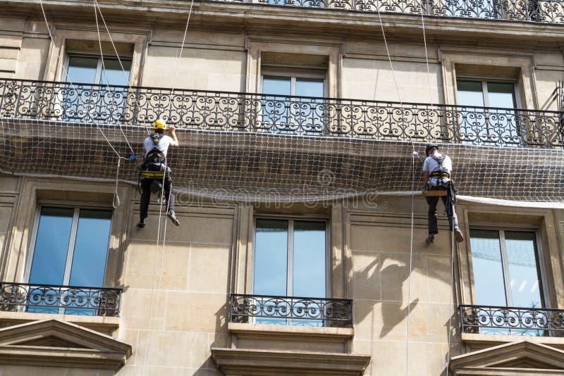 绳索的工作员在老居民住房前面,巴黎 免版税库存图片