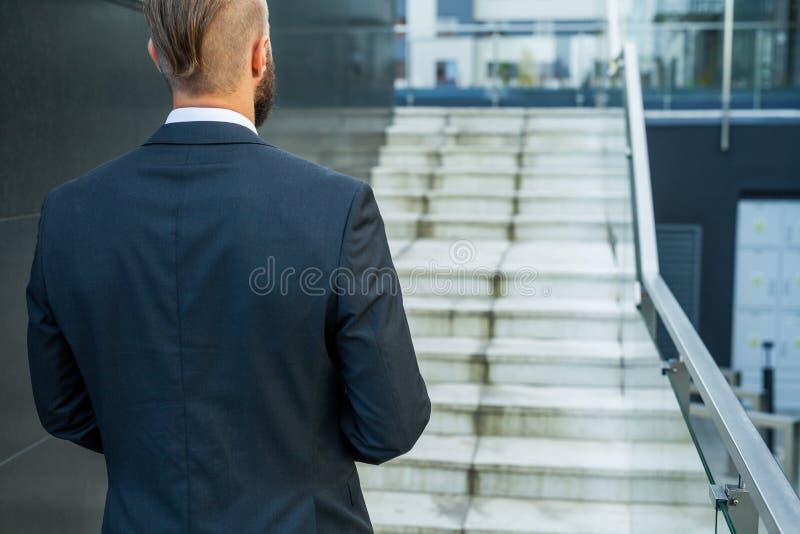 去他的工作的商人 回到视图 免版税库存照片