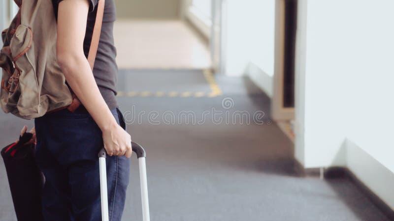 的年轻人旅客走在现代机场终端的后面观点 库存图片