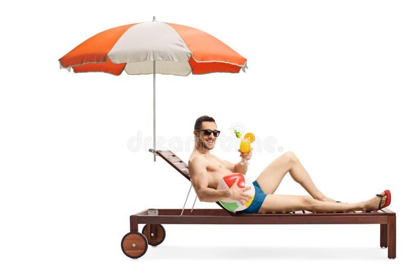 的年轻人sunbed与拿着一个可膨胀的球和鸡尾酒的伞 库存图片