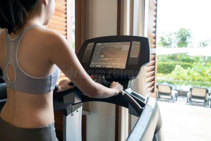 的年轻女人运动员跑在健身房的踏车的后面观点 库存照片