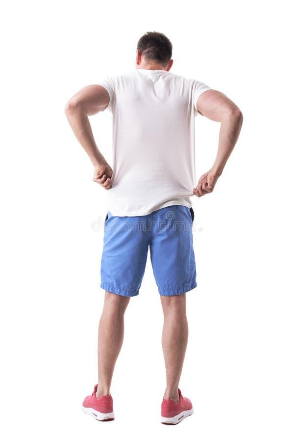 的年轻帅哥调整和投入在夏天衣裳的后面观点 库存图片